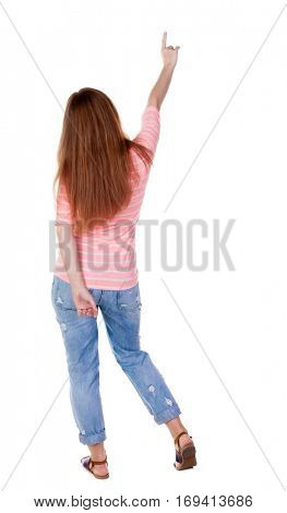 Back view of  pointing woman. beautiful redhaired  girl . girl shows something to someone. Girl in a white T-shirt points a finger at something interesting