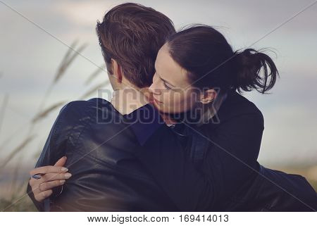 Romantic couple. Girl tenderly embraces the young man. Back view. Outdoor photo.