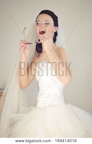 Hilarious bride. Playful model in a wedding dress having fun, fooling around. Indoor photo.
