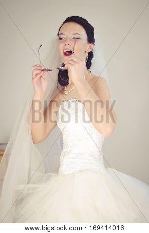 Hilarious bride. Playful model in a wedding dress having fun, fooling around. Indoor photo.