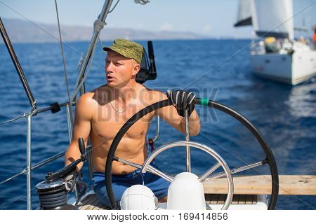 Skipper at the helm controls of a sailing boat during sea yacht race.