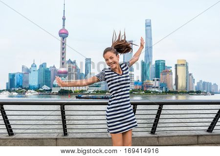 Happy Asian woman tourist having fun dancing of joy in front of Shanghai skyline on The Bund, huangpu river. China travel healthy lifestyle. Happiness concept in urban city.