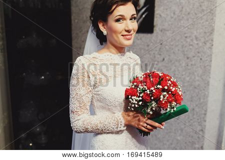 Bride Looks Shy Standing Outside With Her Bouquet