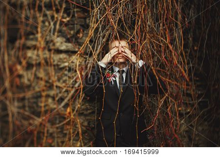 Fiance Closes His Eyes Standing Behind A Dry Vine