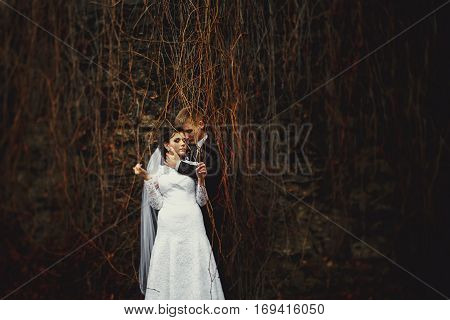 Bride Holds Dry Ivy In Her Hands Hiding Under It With A Fiance