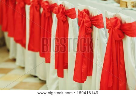 Chairs In Restaurant Covered With White Cloth And Red Bows