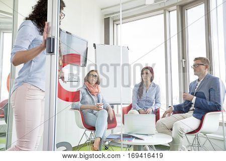 Business people looking at female colleague standing in sliding door