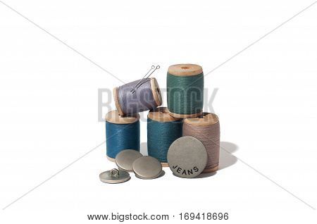 Spool of thread, needle and button isolated on white background.