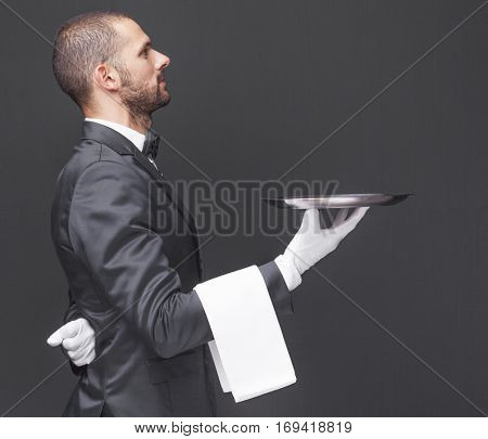 Side view of a waiter in black suit holding a silver tray over dark background