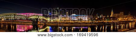 Moscow Russia - January 20 2017: Night winter panorama of the Moskva River embankment: pedestrian bridge Bogdan Khmelnitsky Kiev railway station Moscow-City Redisson Slavyanskaya hotel