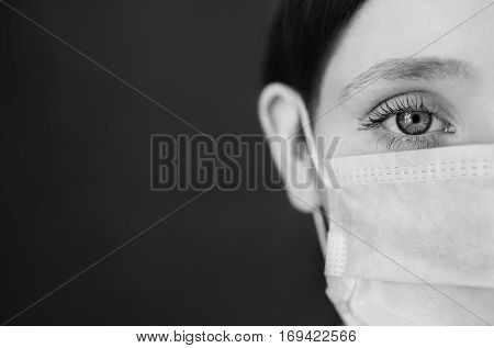 red-haired girl with a medical mask on a red background woman doctor woman with intense look European half of the face hair pinned