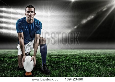 Full length portrait of rugby player placing ball against spotlightand copy space 3d