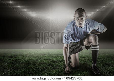 Portrait of confident sportsman kneeling against spotlight and copy space 3d