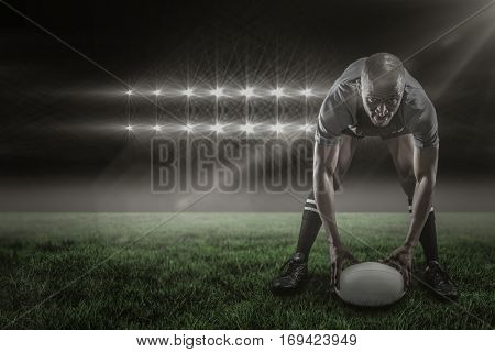 Portrait of sportsman holding ball while playing rugby against spotlights and copy space 3d