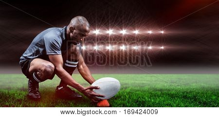 Rugby player keeping ball on kicking tee against spotlights and copy space 3d