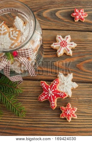 Christmas gingerbread cookies in the shape of snowflake on wooden table.
