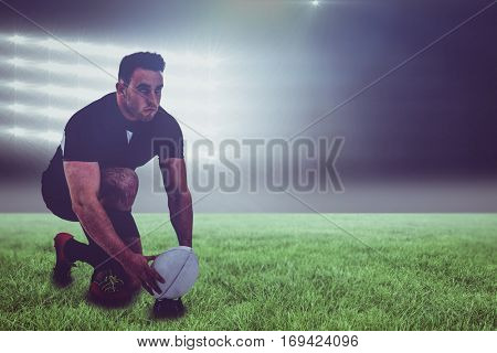 Rugby player getting ready to kick ball against spotlight and copy space 3d