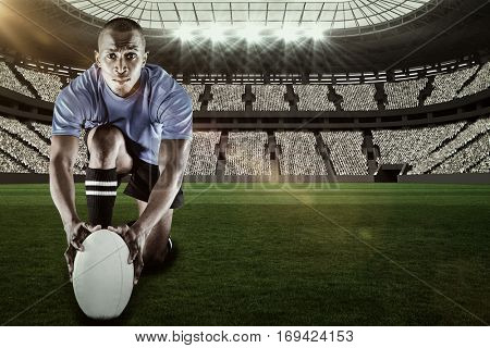 Portrait of rugby player kneeling and holding ball against rugby stadium with copy space 3d