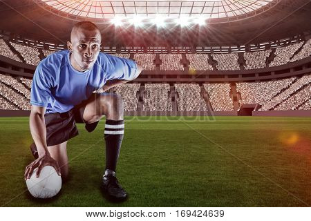 Serious rugby player kneeling while holding ball against rugby stadium with copy space 3d