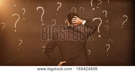 Rear view of a doubtful businessman looking at various question marks drawn on a grey wall