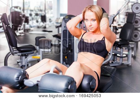 pretty young sportswoman doing abs crunches on bench in gym