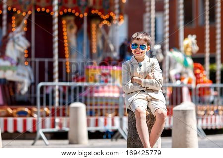 Stylish kid in a nice suit and glasses near the traditional French merry-go-round, Beauvais, France