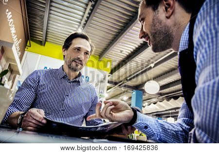 Two businessmen in chekered shirts are working and have a great time in cafe. Work with documents