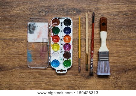 Artistic squirrel brushes tubes of oil paints and watercolors on a wooden background. Used tools for artists students and schoolchildren. Stained with paint brush. The palette of twenty-four colors. Tools for art