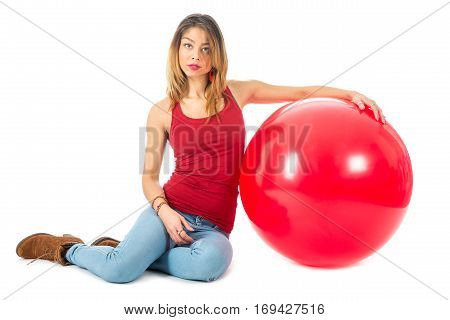 Beautiful woman with red shirt sitting on floor with a big red balloon isolated on white background