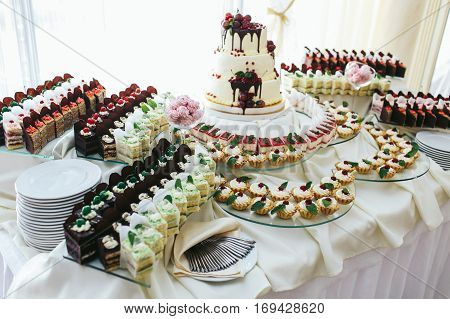 Different Cakes Made Of Black And Whie Chocolate And Fruits Stand On The Dishes