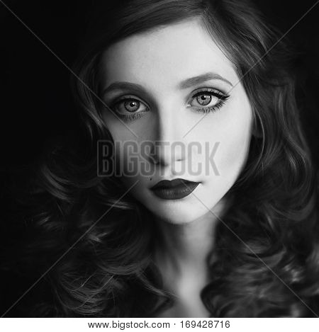 portrait of red-haired girl with big blue eyes and red lips woman with pale skin on a dark background red curly hair
