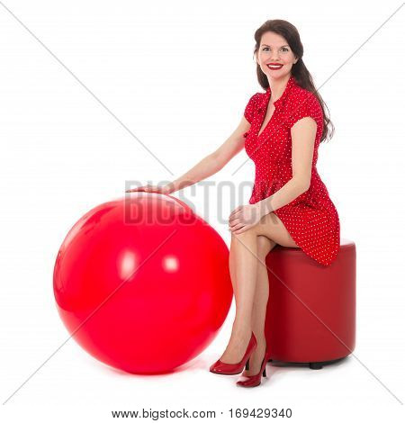 Beautiful woman in red dress sitting on footstool holding a big red balloon; isolated on white background