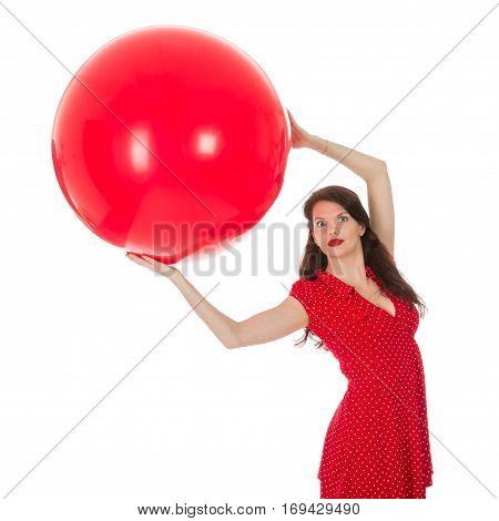 Beautiful woman in red dress holding a big red balloon above her head isolated on a white background