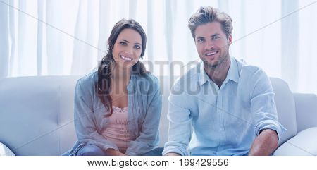 Happy couple doing their accounts sat in a couch