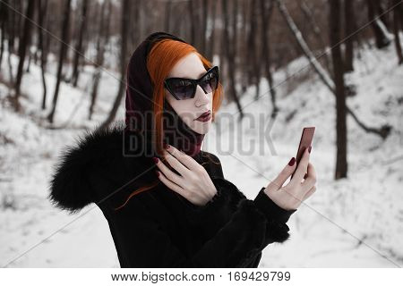 redhead stylish girl with pale skin blue eyes and burgundy red lips with a shawl on her head in a black coat on a background of a winter forest woman with black sunglasses looking in the mirror