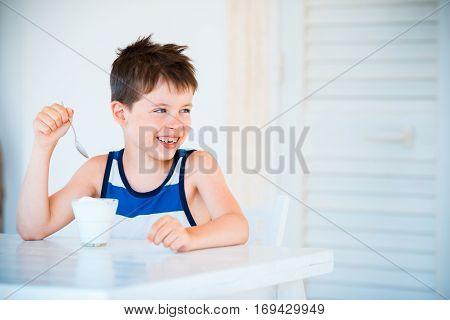 Portrait of smiling cute little boy refuses to eat delicious yogurt