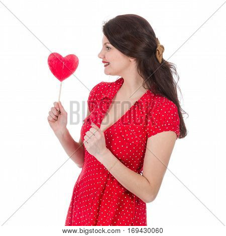 Beautiful woman in red dress eagers a red heart-shaped lollipop in front of her isolated on white