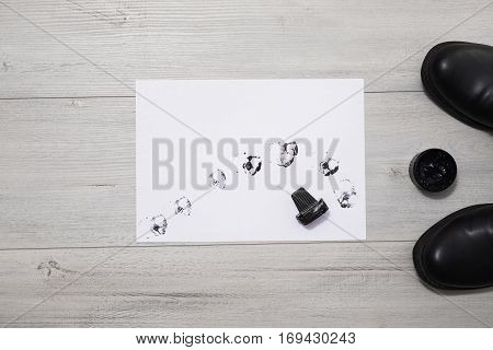 Black leather men's shoes on a gray wooden background shoe polish. The spots of black ink on white paper the prints from the sponge for shoes. Autumn boots . Conceptual idea. shoemaker table.