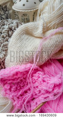 Pink and white wool yarn for knitting, wooden needles and decorative lantern