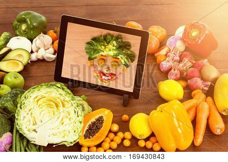 Digital tablet surrounded with fresh fruits and vegetable against smiley face made of confectionary and vegetables