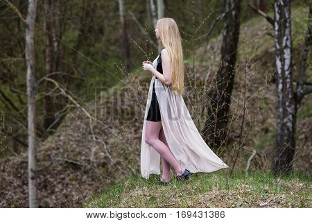 Blonde in dress looking at spring nature. The girl with long hair is in the ravines. Pose the model in a dress. Composition Outdoors