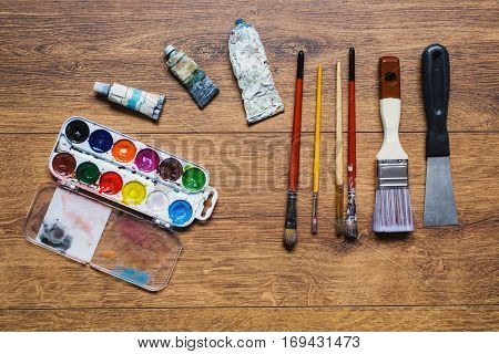 Artistic squirrel brushes tubes of oil paints and watercolors on a wooden background.The palette of twenty-four colors .Used tools for artists and schoolchildren. Tools for art