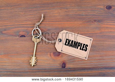 Key and a note on a wooden table with text: Examples.