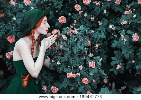 Red-haired girl sniffs white - red roses in the summer garden. Elegant lady in a green hat with a long braid inhales floral fragrance. Vintage retro style. The Age of romanticism