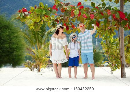 Beautiful family at beach making a self portrait with a mobile phone, Koh Phangan island, Thailand, Asia