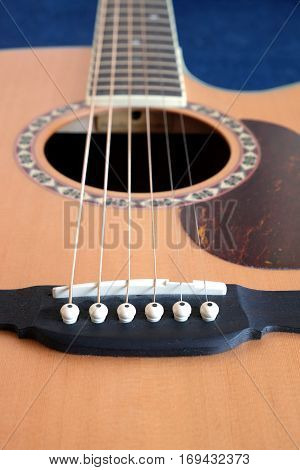 Classic acoustic six strings guitar natural color top from spruce with cutaway fragment with long neck on jeans background vertical view closeup