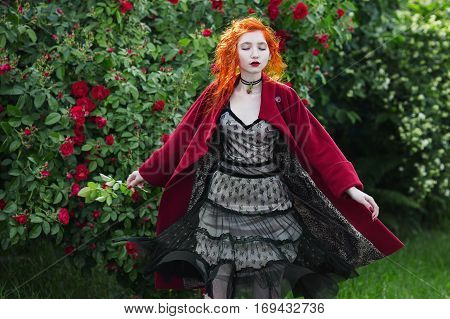 Red-haired girl with pale skin circled in red coat. A woman with a gray dress with tsvetokm on neck on the background of a large bush of red roses. The dress fluttering in the wind. Closed eyes.