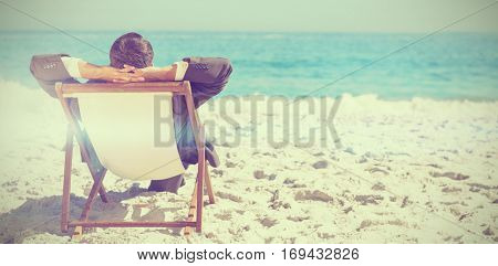 Young businessman relaxing on his sun lounger on the beach with copy space