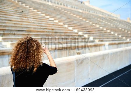 Rear view of elegant woman taking photo on smartphone outside the stadium of the ancient stone stairs chairs