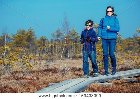 Cute little boy with his mother walking on trail in swamp and having fun, Kemeri national park, Latvia